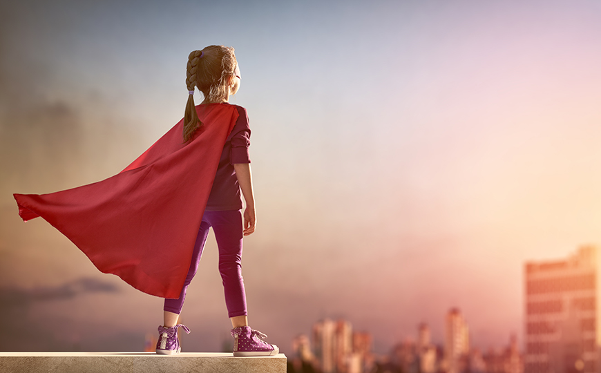 Little Child Girl Plays Superhero Child On The Background Of Su